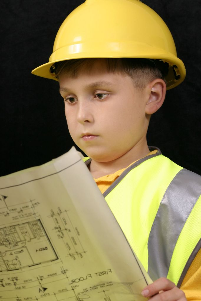 boy in yellow hard hat with documents