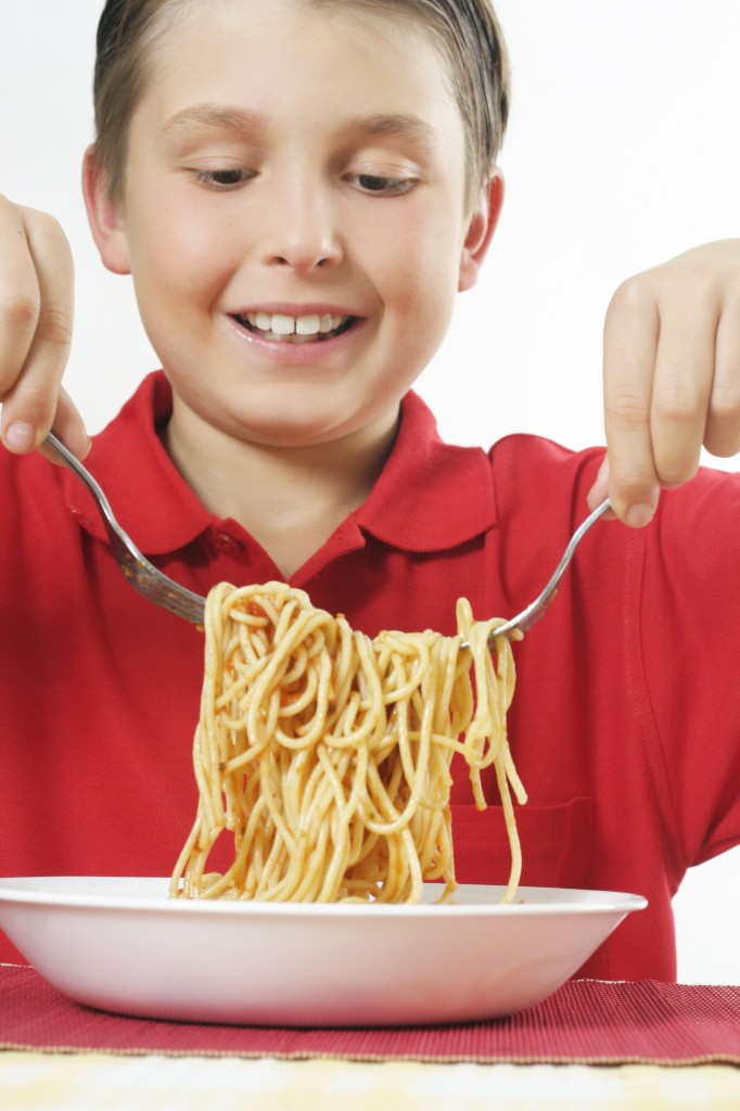 boy with forks full of spaghetti