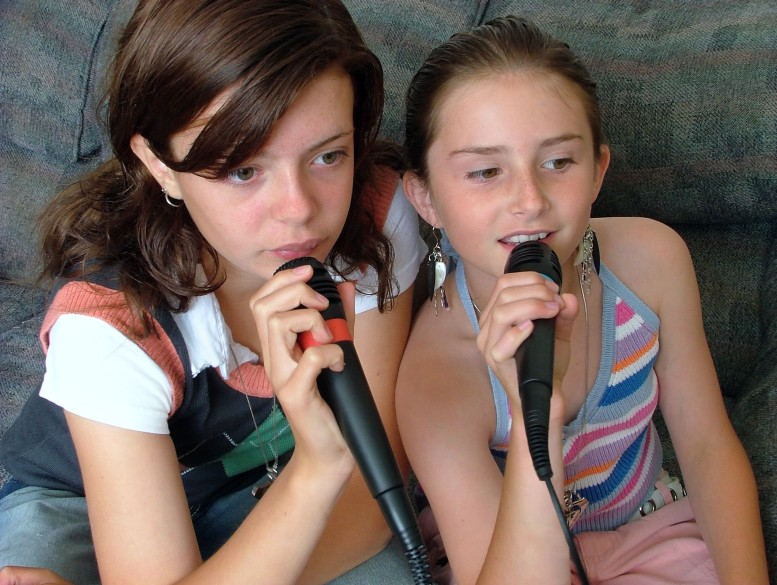 two girls singing with microphones