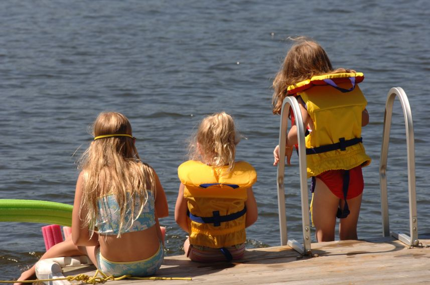 girls by the water with life jackets