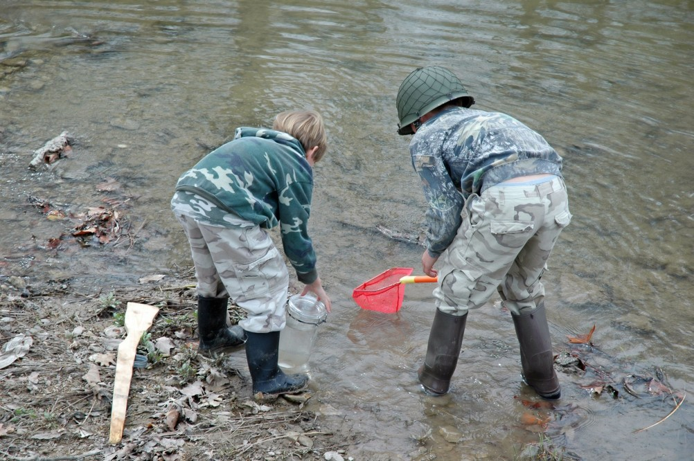 two boys playing in a river