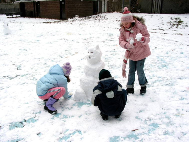 three youth making a snowman