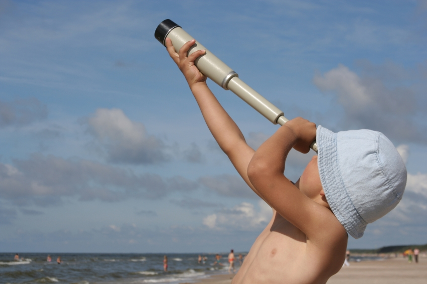 boy with telescope in the beach