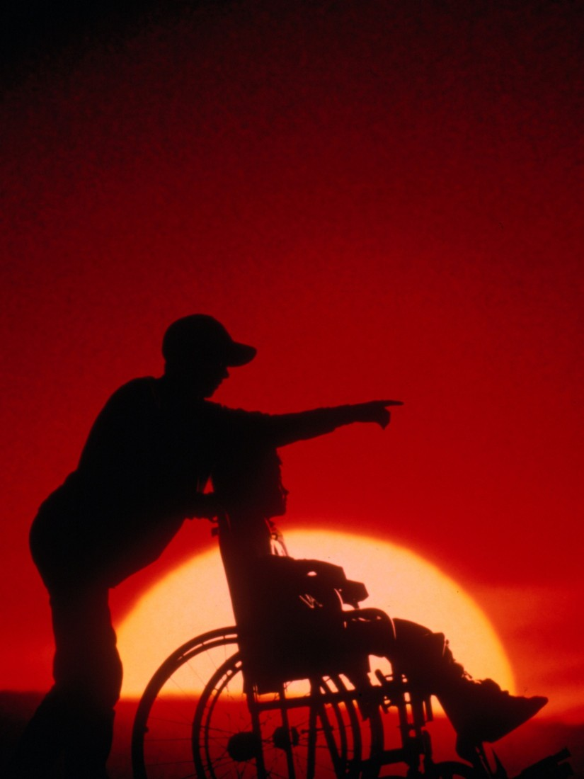 adult pointing to sunrise with person who uses a wheelchair